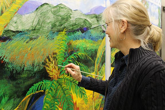 Jean Crossman touching up her mural
